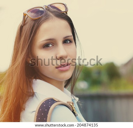 Portrait of a beautiful happy teen girl in sunset light