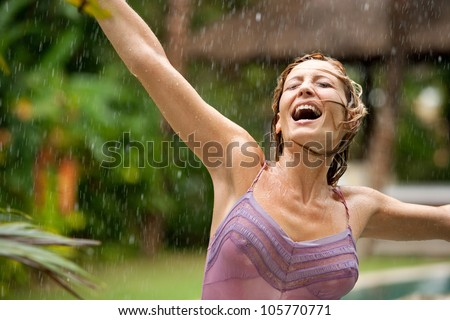 Portrait of a beautiful happy woman enjoying tropical rain falling on her in an exotic garden.