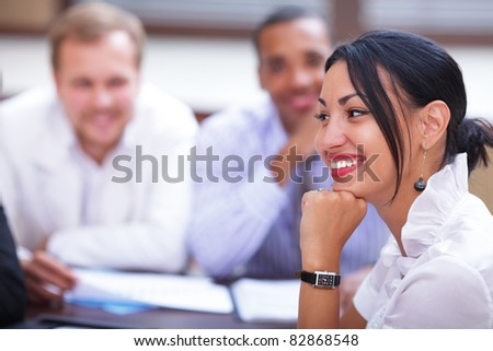 Portrait of a beautiful hispanic business woman at a meeting with colleagues in the background.