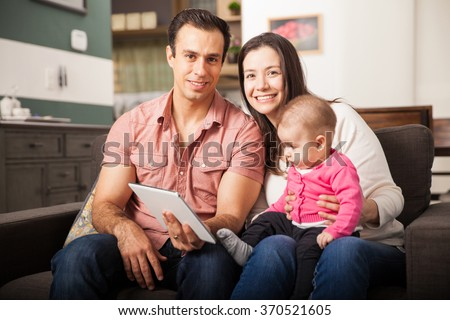 Portrait of a beautiful Hispanic couple using a tablet computer with their baby daughter at home - stock photo