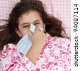 Portrait of a beautiful hispanic girl sick with the flu and covering his nose with a handkerchief laying in a bed with pink sheets - stock photo