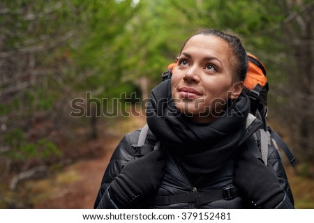 Portrait of a beautiful hispanic woman hiking in the pine forest alone, a solo expedition camping trip - stock photo