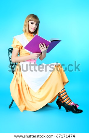 Portrait of a beautiful housewife reading a book. Studio shot. - stock photo