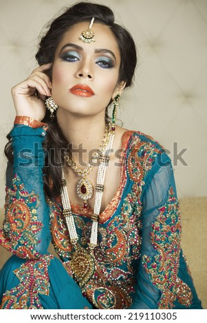 portrait of a beautiful Indian bride wearing traditional eastern outfit. - stock photo