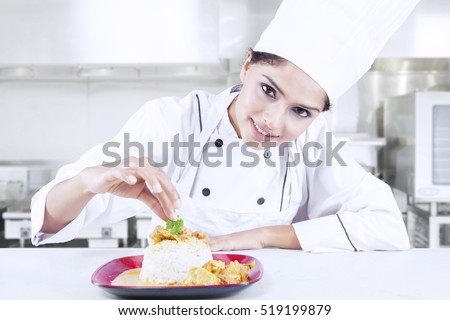 Portrait of a beautiful Indian chef preparing delicious meal in the restaurant kitchen