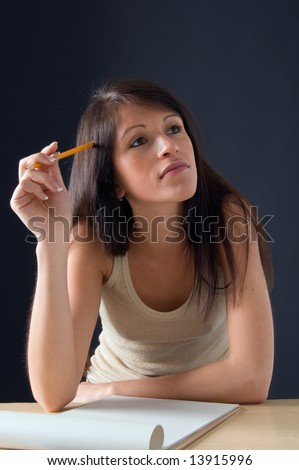 Portrait of a beautiful isolated  teenager  student. An attractive young student posing at her desk. Picture of a pretty girl isolated on a dark background. - stock photo
