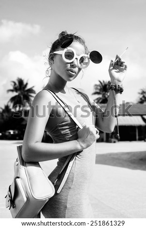 portrait of a beautiful lady with cigar. Outdoors lifestyle. Toned black and white - stock photo
