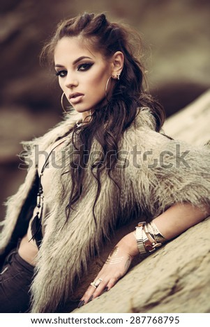 Portrait of a beautiful lady with flash tottoos posing outdoors near the sea - stock photo