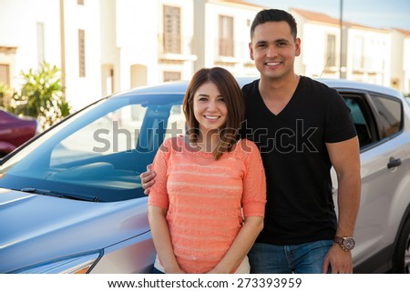 Portrait of a beautiful Latin couple standing next to their new car and smiling - stock photo