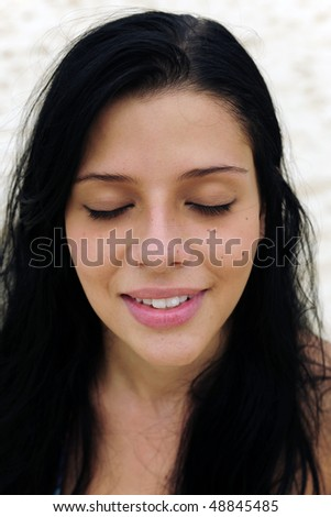 portrait of a beautiful latin girl eyes closed on the beach - stock photo