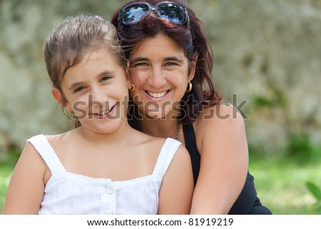 Portrait of a beautiful latin mother and daughter in a park - stock photo