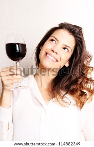 Portrait of a beautiful, latin Woman drinking red wine. - stock photo