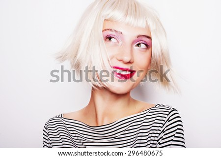 Portrait of a beautiful laughing blonde girl in a striped dress in the studio  on a white background - stock photo