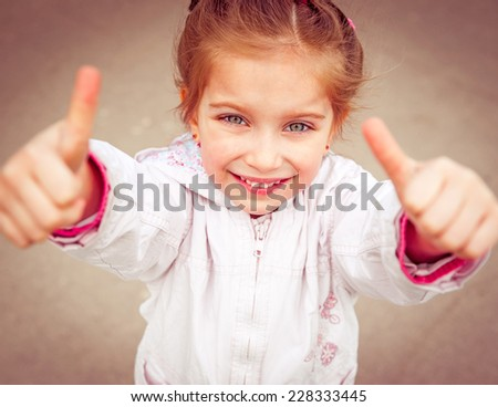 Portrait of a beautiful liitle girl shows thumb close-up - stock photo