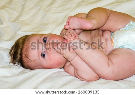 Portrait of a beautiful little baby girl in a diaper that gnaws his leg