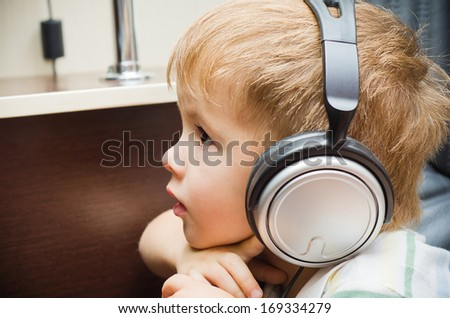 Portrait of a beautiful little boy in headphones - stock photo