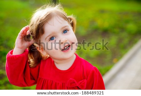 portrait of a beautiful little girl. child walking in the park. meadow with dandelions, child smelling flowers - stock photo