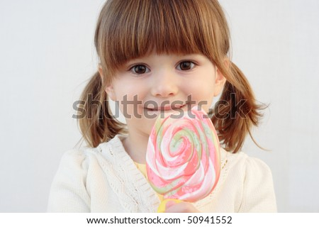 Portrait of a beautiful little girl holding a big round swirl lollipop - stock photo