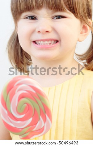 Portrait of a beautiful little girl holding a big swirl lollipop - stock photo