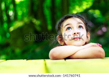 Portrait of a beautiful little girl in the forest. With hands on chin looking up - stock photo