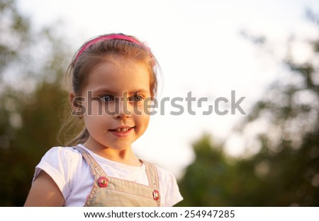 Portrait of a beautiful little girl looking thoughtful in the light of a late afternoon sun - stock photo