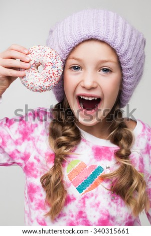Portrait of a beautiful little girl taking a sweet cake wearing colorful sweater and violet knitted hat. - stock photo