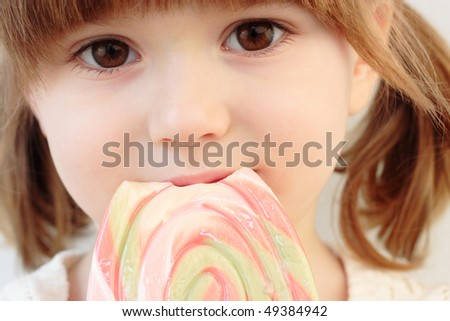 Portrait of a beautiful little girl with a big  swirl lollipop - stock photo