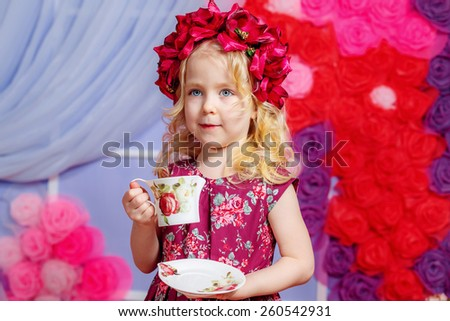 portrait of a beautiful little girl with a cup of tea - stock photo