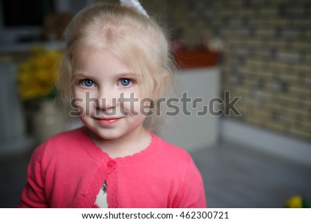 Portrait of a beautiful little girl with flowers on background of brick wall