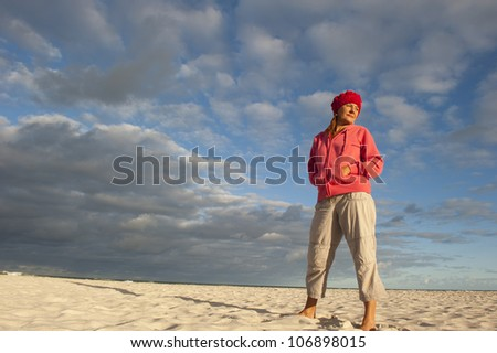 Portrait of a beautiful looking middle aged woman standing in casual pose on beach, wearing pink sweater, with soft sunlight on her face and storm clouds over ocean as background and copy space. - stock photo
