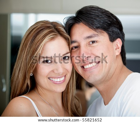 Portrait of a beautiful loving couple smling Handsome man smiling with a woman behind him - stock photo