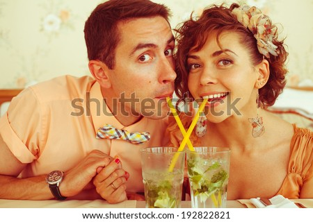 Portrait of a beautiful married couple of hipsters in trendy clothing drinking mojito through crossed sippers in vintage cafe. Butterfly accessories. Wedding day. Close up. Indoor shot - stock photo