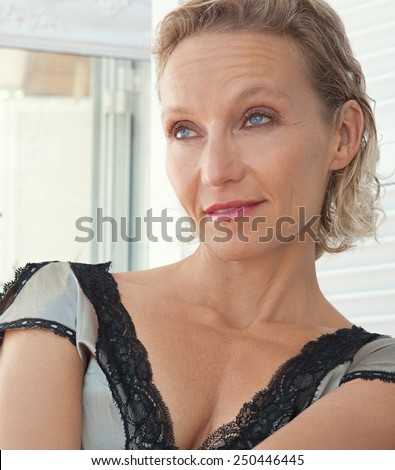 Portrait of a beautiful mature senior woman lounging on a day bed, relaxing at home while in silk lingerie dress, looking away being thoughtful, outdoors. Summer beauty middle age lifestyle. - stock photo