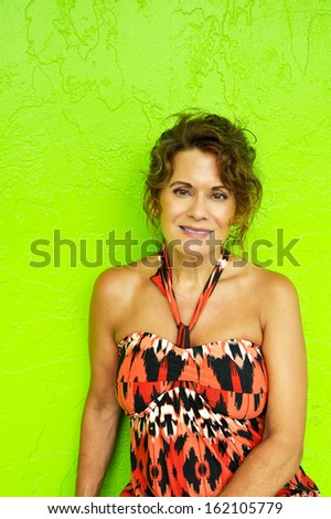 Portrait of a Beautiful Mature Woman Against a Bright Green Wall   - stock photo