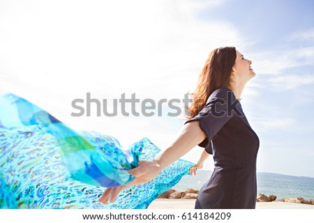 Portrait of a beautiful mature woman breathing fresh air by the sea, holding a floating fabric scarf in the breeze on sunny day, outdoors. Well being and healthy lifestyle, dreamy positive exterior.