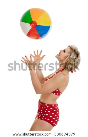 Portrait of a beautiful mid 30s woman dressed in vintage retro polka dot bikini throwing a beach ball in the air isolated on white