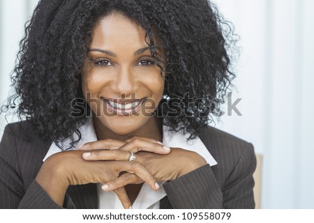 Portrait of a beautiful middle aged African American woman or businesswoman sitting relaxing & smiling - stock photo