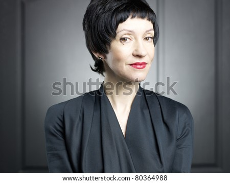 Portrait of a beautiful middle aged woman against black background - stock photo