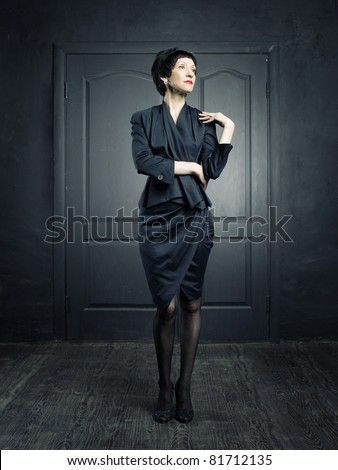 Portrait of a beautiful middle aged woman in black interior