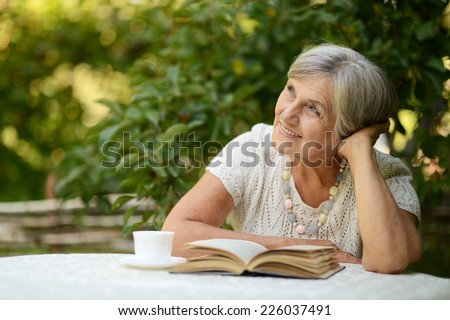 Portrait of a beautiful middle-aged woman outdoors at the table - stock photo