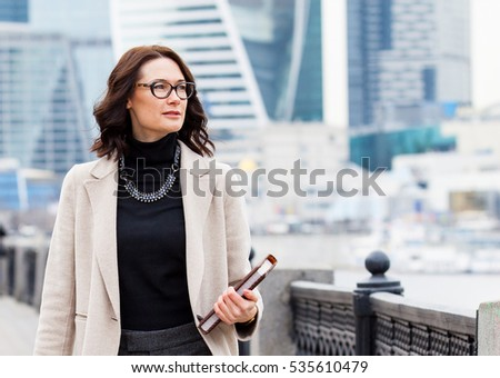 portrait of a beautiful middle-aged woman with books in hand on the background of skyscrapers in the business district