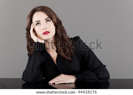 Portrait of a beautiful middle aged woman with red lips looking up  thinking pensive on gray background - stock photo
