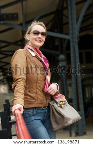 Portrait of a beautiful middle aged woman with sunglasses and bag smiling outdoors - stock photo