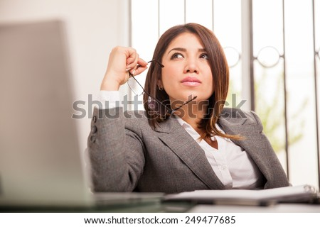 Portrait of a beautiful mixed-race business woman looking up and daydreaming at her office - stock photo