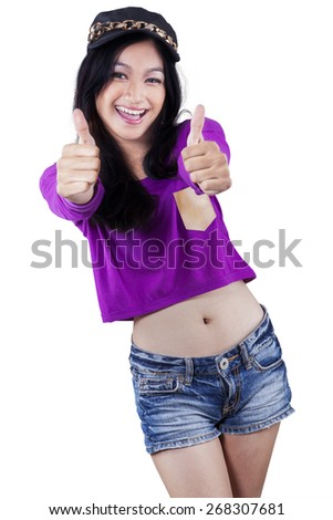 Portrait of a beautiful modern teenage girl with casual clothes showing thumbs up in studio - stock photo