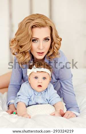 Portrait of a beautiful mom blonde and a little girl baby with blue eyes in a striped blue dress lying on white bed.