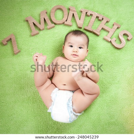 Portrait of a beautiful 7 months baby girl lying down on a blanket - stock photo