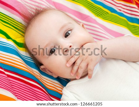 Portrait of a beautiful 6 months baby lying on bed and sucking thumb - stock photo