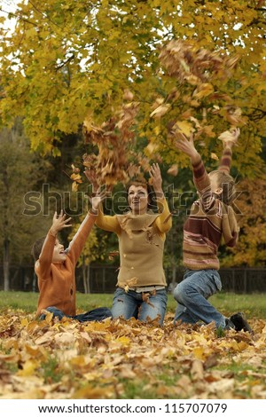 portrait of a beautiful mother and her children throwing autumn leaves - stock photo
