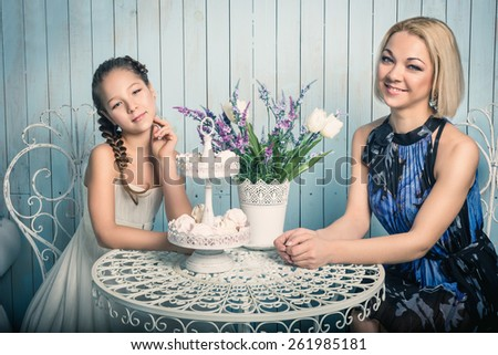 Portrait of a beautiful mother and her daughter sitting at the table  in a kitchen - stock photo